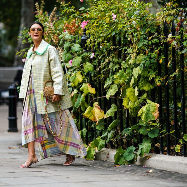 london, england   september 16 a guest wears sunglasses, a checked jacket with green collar, a golden bag, a checked dress, shoes, during london fashion week september 2019 on september 16, 2019 in london, england photo by edward berthelotgetty images