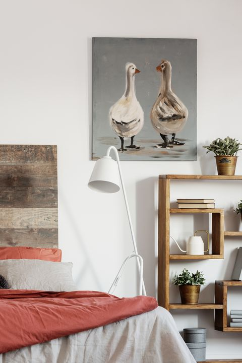 Real photo of a rustic ducks painting hanging on a white wall in bright bedroom interior