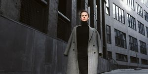Girl in a gray coat  against the backdrop of modern architecture