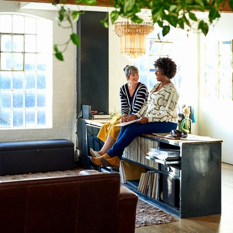 women relaxing together, sitting on sideboard in open plan living room, listening to records, friendship, lifestyle, bonding