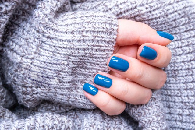 stylish women's manicure in blue on the background of a knitted gray jacket the concept of self care