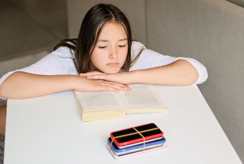 Social media and gadget detox. Sad preteen girl reading book and looking at pile of smartphones at table taken from her. No phone punishment.