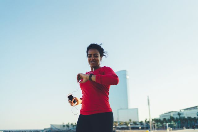 woman checking pulse on smart watch while jogging