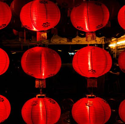 rows of brightly lit red chinese lanterns at night
