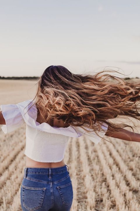 summer girl enjoying nature on yellow field beautiful young woman dancing outdoors long hair in the wind happiness and lifestyle back view