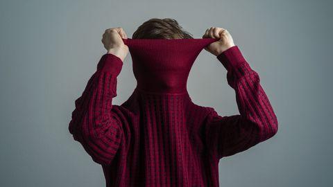 een man trekt uit verlegenheid een trui over zijn hoofd