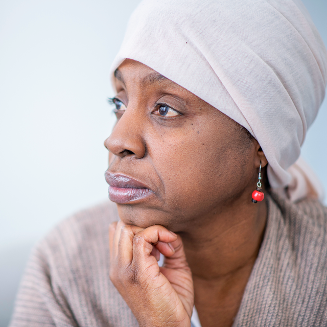 black woman looking off while wearing head scarf