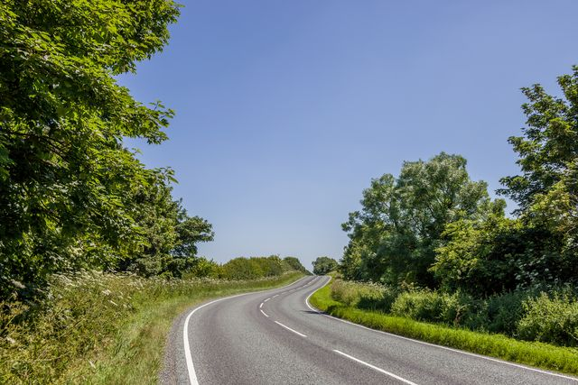 country empty road in summer with clear blue sky, england uk