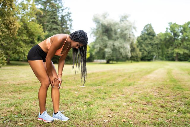 athlete in pain holding her left knee a she bends down