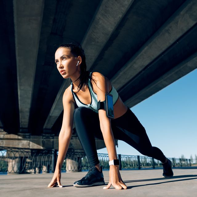 runner woman ready to run in running start pose on the city industrial background sprinter training outdoor