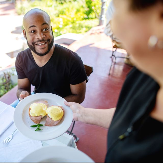 personal perspective of a waiter serving breakfast to a friendly guest at a cafe restaurant on an outdoor porch veranda  there is guava juice on the table and flowers and a cup and saucer  the young guy is being served breakfast  he is an attractive young african man in his twenties