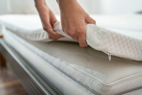 mattress topper being laid on top of the bed