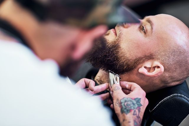 cropped shot of a handsome young man getting his beard trimmed and lined up at a barbershop