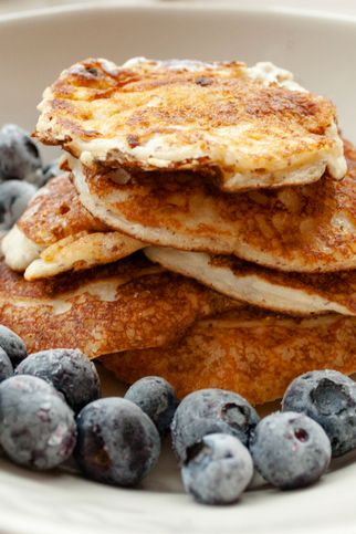 low carb keto diet pancakes from almond coconut flour with blueberries, cream on white plate background close up view selective focus copy space ketogenic concept