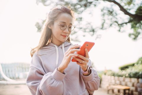 pretty asian young lady using smartphone joyfully in park