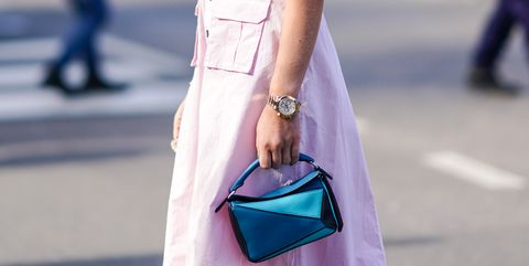 milan, italy   february 23 a guest wears a watch, a pink dress, a blue loewe bag, outside boss, during milan fashion week fallwinter 2020 2021 on february 23, 2020 in milan, italy photo by edward berthelotgetty images