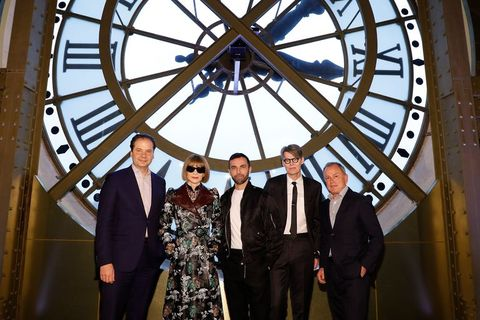 Max Hollein, Anna Wintour, Nicolas Ghesquiere, Andrew Bolton, and Michael Burke pose for a photo in front of a giant clock.