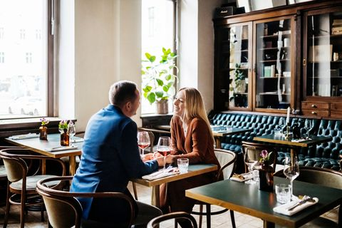 a couple holding hands while sitting down at a table and drinking red wine in a restaurant for lunch together,
