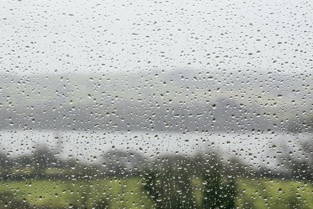 looking out through rain drops on a window to a rural landscape