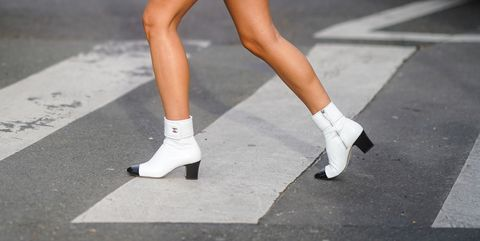 paris, france   march 03 a guest wears purple leather shorts, a pink top, white pointy chanel boots, outside lacoste, during paris fashion week   womenswear fallwinter 20202021 on march 03, 2020 in paris, france photo by edward berthelotgetty images