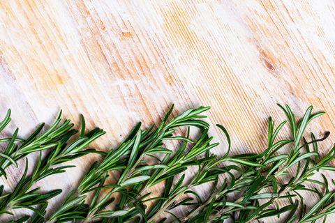 Brins verts de romarin sur une surface en bois