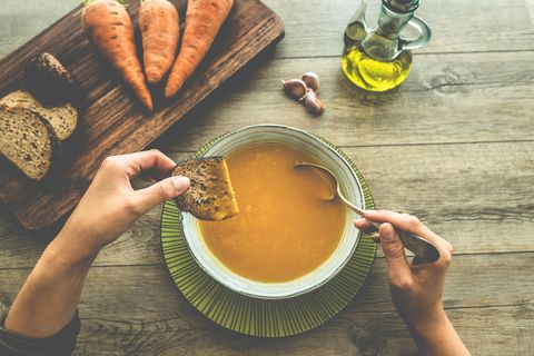 Top view of young woman eating carrot soup with bread - Food and healthy lifestyle concept - Main focus on right hand
