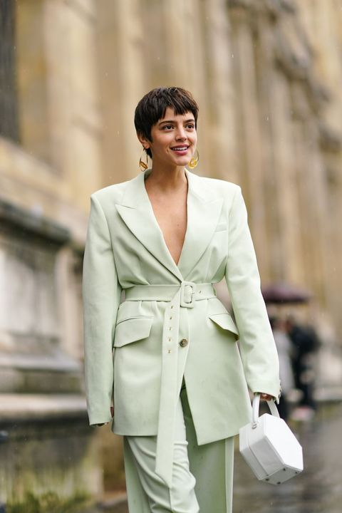 paris, france   march 01 a guest wears earrings, a pale green low neck oversized jacket, a belt, large and flowing pants,a white bag, during paris fashion week   womenswear fallwinter 20202021, on march 01, 2020 in paris, france photo by edward berthelotgetty images