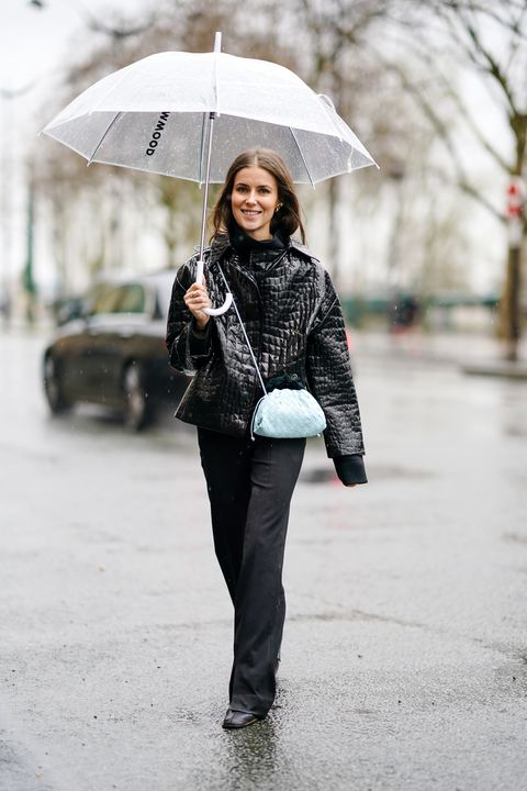 paris, france   march 01 a guest wears a crocodile pattern black leather jacket, a pale blue quilted bag, black flared pants, black leather boots, during paris fashion week   womenswear fallwinter 20202021, on march 01, 2020 in paris, france photo by edward berthelotgetty images