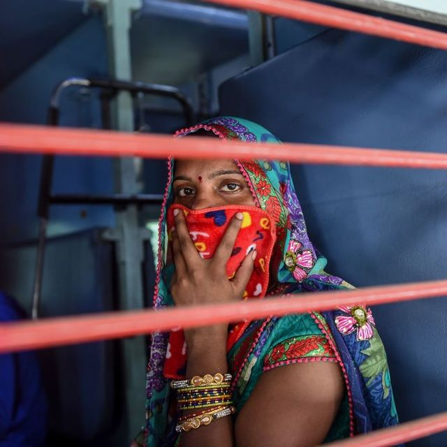 a migrant worker looks out of a compartments window as she sits inside a special train going to agra in uttar pradesh state during a government imposed nationwide lockdown as a preventive measure against the covid 19 coronavirus, at sabarmati railway station on the outskirts of ahmedabad on may 2, 2020 photo by sam panthaky  afp photo by sam panthakyafp via getty images