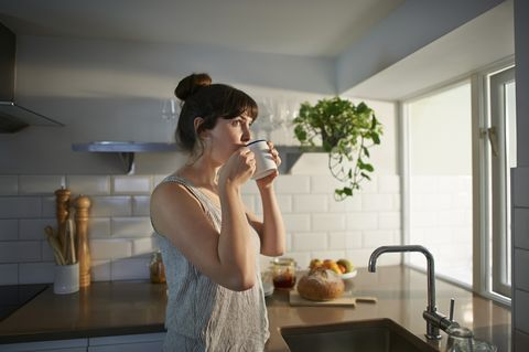 a woman standing in her kitchen drinks from a mug