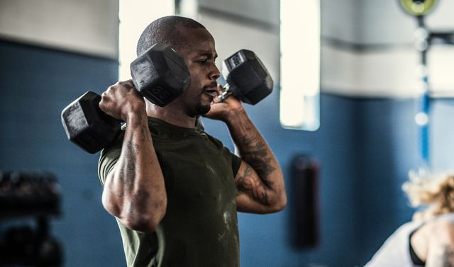 man lifting dumbells at cross training gym
