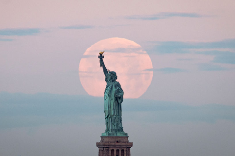 may's super flower moon sets behind the statue of liberty in 2020