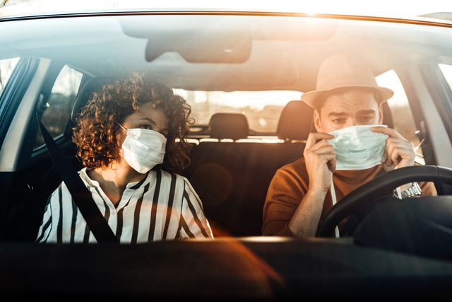 corona virus pandemic concept breathing through a medical mask because of the danger of getting the flu virus, influenza infection enjoying travel beautiful young couple sitting on the front passenger seats and smiling while handsome man driving a car