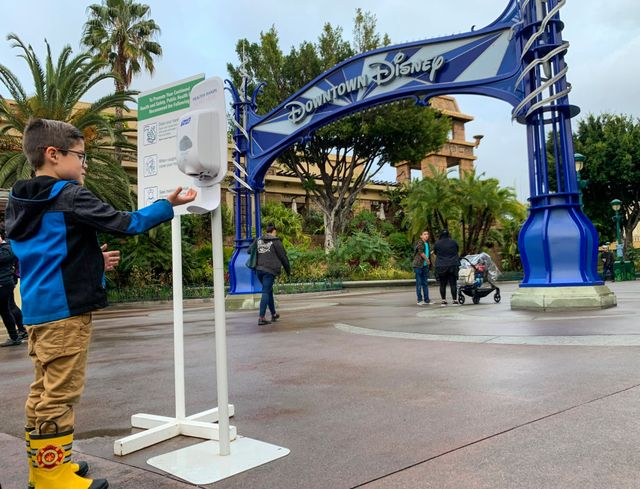 anaheim, ca   march 13 a young visitor to downtown disney uses a hand sanitizer station during the day last before disneyland closes because of the coronavirus covid 19 outbreak in anaheim, ca, on friday, march 13, 2020 photo by jeff gritchenmedianews grouporange county register via getty images