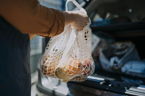 an asian chinese  female delivery person getting the groceries and fruit her customer order online shopping in recycle bags from her car trunk and deliver it to her customer