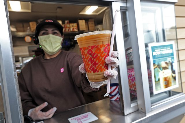 norwell, ma   march 17  a dunkin worker hands a coffee out of a drive thru window wearing gloves and a mask as the coronavirus continues to spread on march 17, 2020 in norwell, massachusetts staff photo by matt stonemedianews groupboston herald