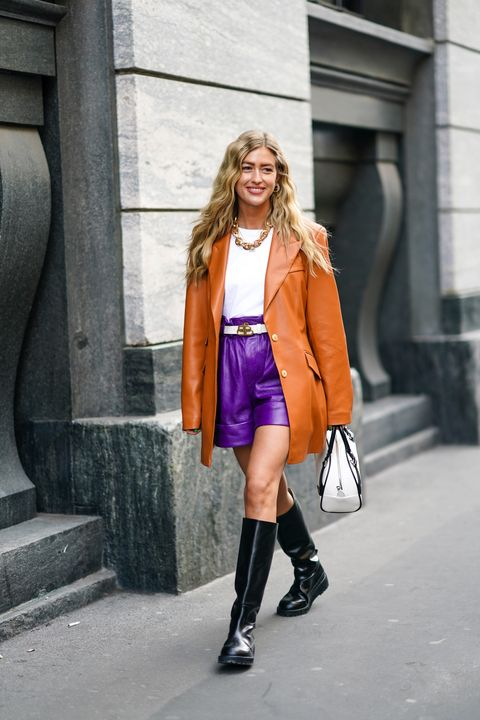 milan, italy   february 22 emili sindlev wears earrings, a necklace, a white top, a balenciaga white belt, a tan color leather long jacket, purple leather shorts, black knee high boots, a white and black prada bag, outside philosophy, during milan fashion week fallwinter 2020 2021 on february 22, 2020 in milan, italy photo by edward berthelotgetty images