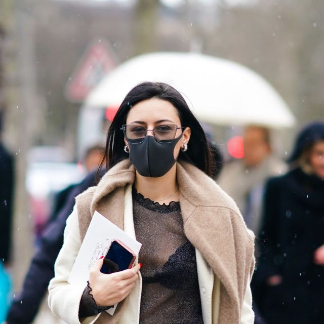 paris, france   february 29 a guest wears glasses, a brown wool pullover over the shoulders, a white long coat, a mesh black top, black bras, black pants, earrings, a protective face mask in a context of coronavirus covid 19 breakout, during paris fashion week   womenswear fallwinter 20202021, on february 29, 2020 in paris, france photo by edward berthelotgetty images