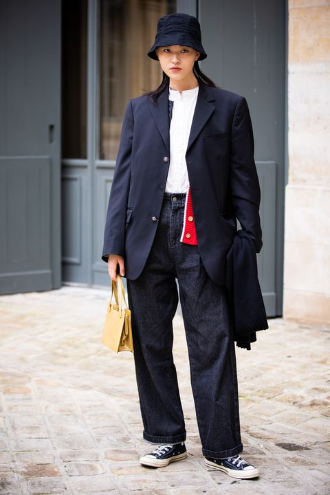 paris, france   march 03 a model, wearing a white shirt, dark blue jeans, black blazer, black hat, black sneakers and yellow bag, is seen outside valentin yudashkin, during paris fashion week   womenswear fallwinter 20202021  day nine on march 03, 2020 in paris, france photo by claudio laveniagetty images