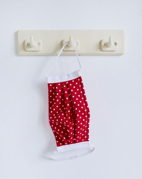 Still life of a red self made face mask hanging at a coat hook, DIY sewing project