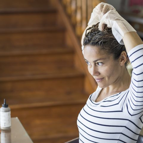 home made hair dye at home for beauty young caucasian woman looking at the mirror   stay at home concept for coronavirus emergency worldwide pandemic contagion