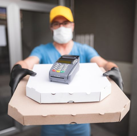 deliveryman with protective medical mask holding pizza box and pos wireless terminal for card paying   days of viruses and pandemic, food delivery to your home and safety hygiene measures