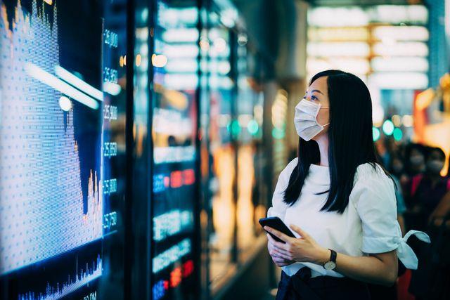 impacto económico tras el covid 19 mujer mirando tabla de finanzas con mascarilla
