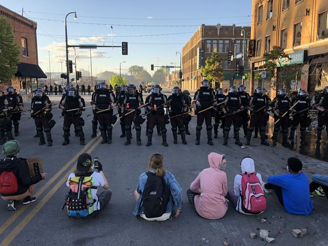 topshot   people sit on the street in front of a row of police officers during a rally in minneapolis, minnesota, on may 29, 2020 after the death of george floyd, a black man who died after a white policeman kneeled on his neck for several minutes   demonstrations are being held across the us after george floyd died in police custody on may 25 photo by kerem yucel  afp photo by kerem yucelafp via getty images