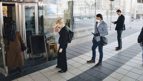 mensen staan met afstand van elkaar in de rij voor een winkel
