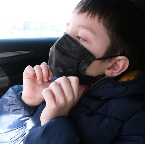 a teenage boy in car putting on surgical medical black face mask as a protection against virus disease, coronavirus covid 19 prevention