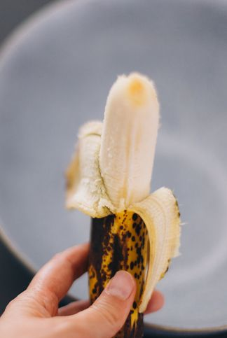 mexico, queretaro, queretaro   april 6, 2020 female hand holding a peeled banana over a ceramic bowl series of images of the process of making vegan banana bread