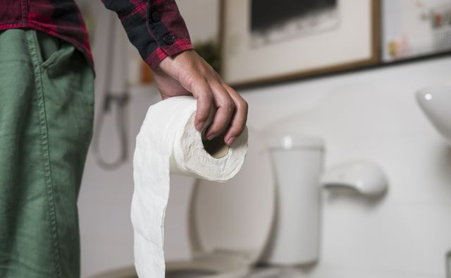 midsection of man with toilet paper standing in bathroom