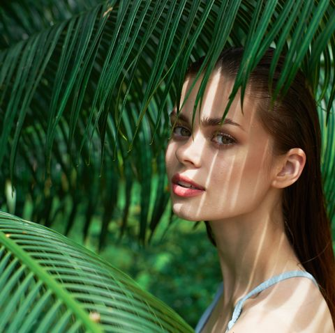 young woman with clean skin after a spa procedure is resting in the shade of a fern on a tropical island