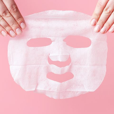 female hands hold white fabric mask on a pink background